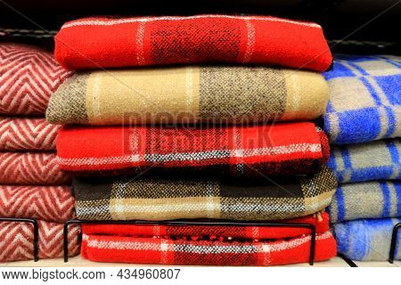 A Stack Of Beautiful Woolen Blankets In Red, Blue, Yellow, Pink. A Pile Of Soft Warm Blankets In The
