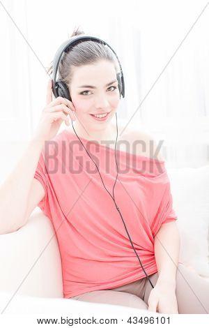 Young Girl enjoys listening music in headphones