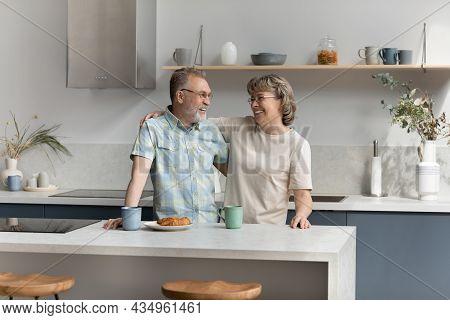 Bonding Affectionate Older Couple Talking In Kitchen.