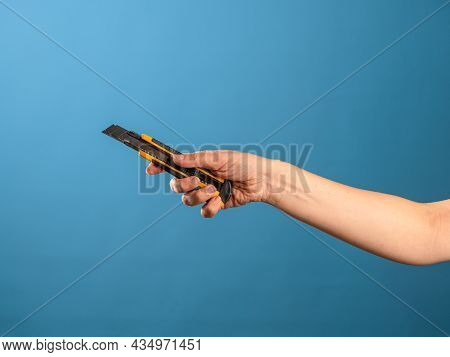 Cut Or Shorten Something, Cut It Out. A Female Hand Holds A Stationery Knife With A Retractable Blad