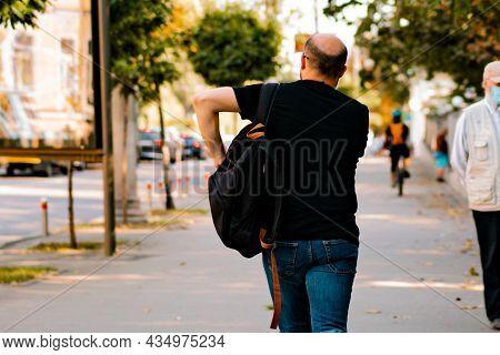 Balding Man Strolling Through The City Street With Black Backpack. Transplantation. Procedure. Aging