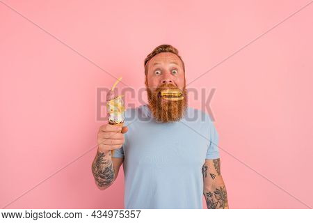 Amazed Man With Beard And Tattoos Is Undecided If To Eat An Icecream Or A Sandwich With Hamburger