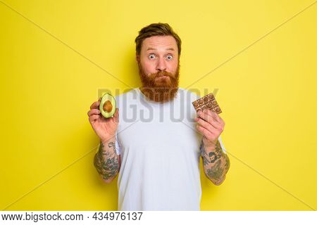 Doubter Man With Beard And Tattoos Holds Avocado And Chocolate