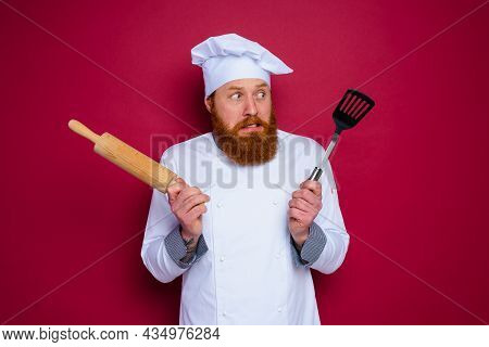 Doubter Chef With Beard And Red Apron Chef Holds Wooden Rolling Pin