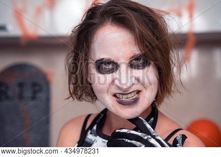 Portrait Of Young Wild Woman With Creepy Makeup, Red Demonic Eyes And A Gaze, Wearing Costume For Th