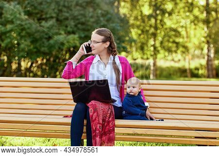Woman With Baby Makes Telework In Park Using Laptop.