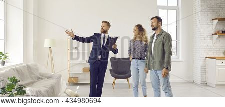 Real Estate Agent Giving Young Customers Tour About Rooms In New House Or Apartment