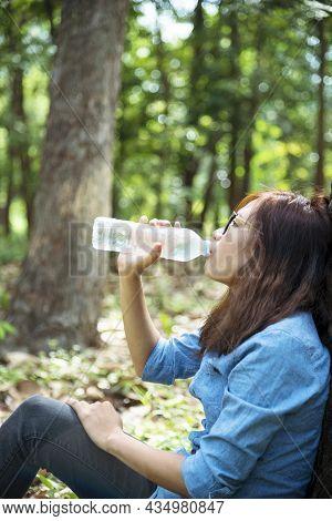 Young Woman Drinking Water From Bottle In Green Garden Park. Asian Female Drinking Water Bottle Heal