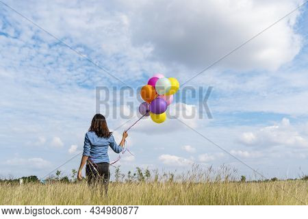 Woman Holding Balloons Running On Green Meadow White Cloud And Blue Sky With Happiness Cheerful And