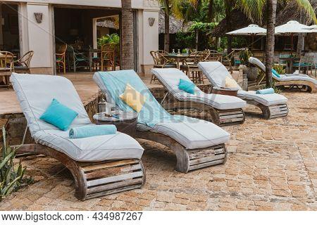 Blank Wooden Loungers in a Row in Luxury Hotel boho styleBlank Wooden Loungers in a Row in Luxury Hotel boho style