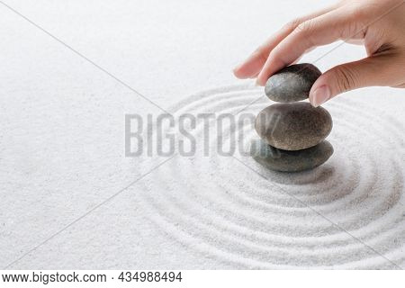 Hand stacking zen stones on the sand wellness background