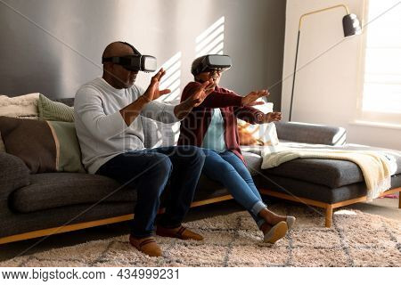 Happy african american senior couple wearing vr headset and having fun at home. retirement lifestyle, technology and spending time at home.