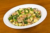 Plateful of potato gnocchi with spicy Italian sausages, rapini, crimini mushrooms and onions. poster