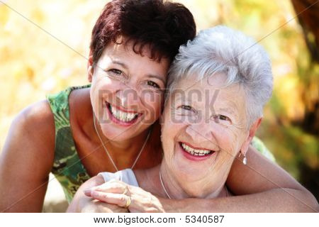 close-up portrait of a beautiful senior mother and daughter smiling at the camera poster