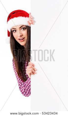 Surprised beautiful girl in Santa Claus hat with blank signboard, isolated on white background