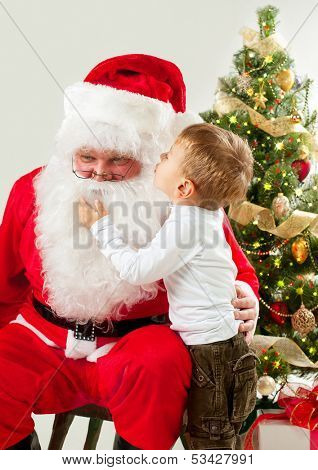Santa Claus and Little Boy. Christmas Scene. Boy Telling Wish in Santa Claus's Ear in front of Christmas Tree