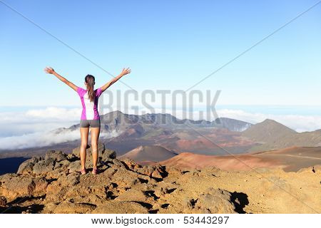 Hiking woman on top happy and celebrating success. Female hiker on top of the world cheering in winning gesture having reached summit of mountain, East Maui Volcano, Haleakala national park Hawaii. poster