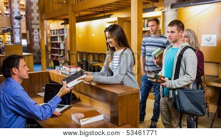 Young students in a row at the counter in college library