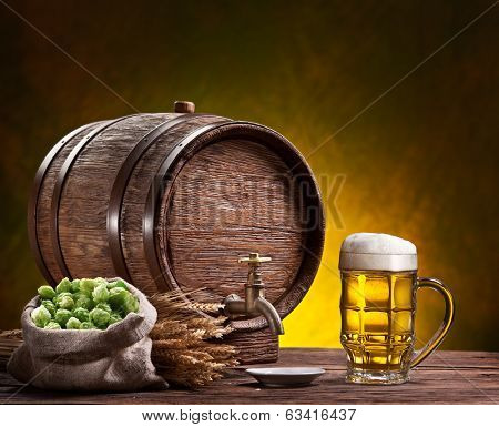 Beer glass, old oak barrel and wheat ears on wooden table.