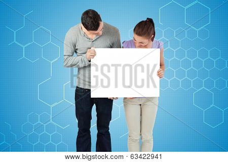 Attractive young couple showing card against chemical structure in blue and white poster