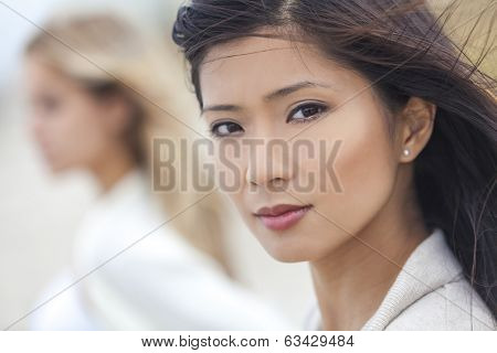 Outdoor profile portrait of a beautiful thoughtful Chinese Asian young woman or girl with blond female friend at beach