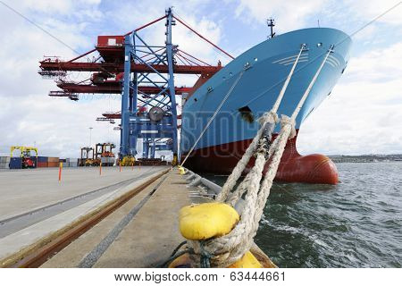container ship mired at quayside, container cranes in action