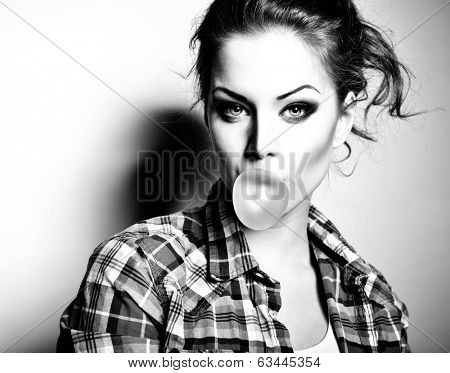 Beautiful teen girl inflating bubble of chewing gum. Modern fashion girl. Black and white. poster