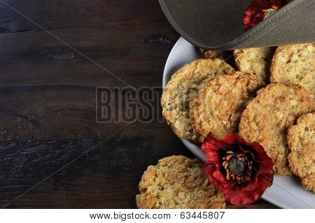 Australian Army Slouch Hat And Traditional Anzac Biscuits On Dark Recycled Wood With Remembrance Red