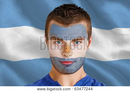 Composite image of serious young argentina fan with facepaint against argentinian flag