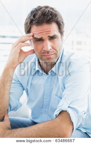 Wincing man with headache sitting on the couch looking at camera at home in the living room