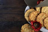 Australian army slouch hat and traditional Anzac biscuits on dark recycled wood with remembrance red poppy for Anzac Day or Remembrance Armistice Day with copy space. poster