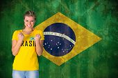 Excited football fan in brasil tshirt against brazil flag in grunge effect poster