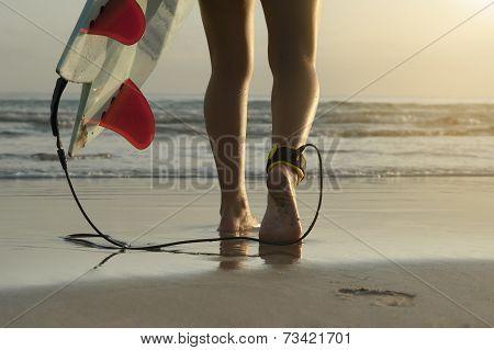 Young beautiful surfer girl walking along beach with surfboard