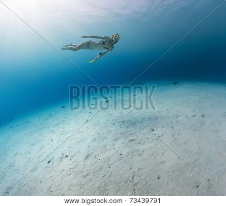 Young lady skin diving in tropical sea over sandy bottom