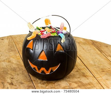 Black plastic pumpkin filled with candy wooden table