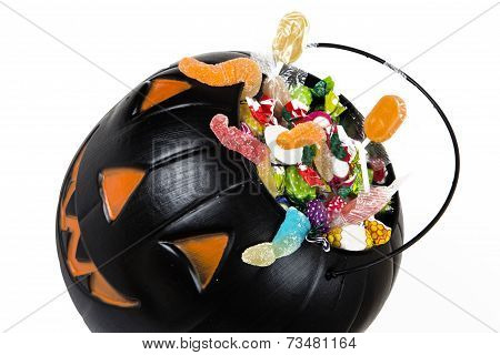 Black plastic pumpkin filled with candy isoleted