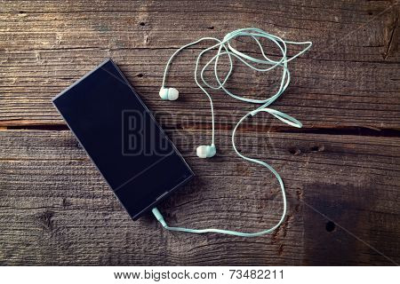 Small headphones with mobile phone on wooden desk