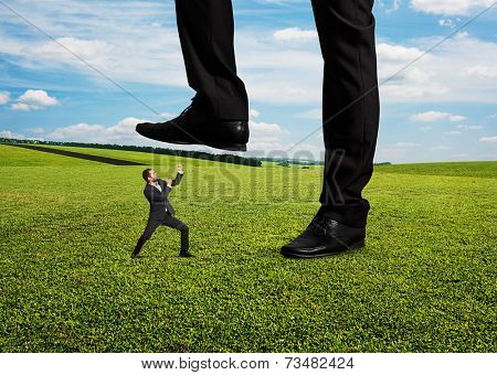 concept photo of conflict between subordinate and boss. angry young businessman showing fist and looking up at his boss. photo at outdoor