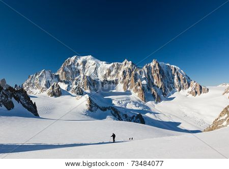 Ski mountaineers ascend the Vallee Blanche glacier. In background the est face of Mont Blanc. Chamonix, France, Europe.