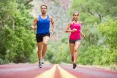 Running young people - two runners jogging on road in nature training for marathon run. Multicultural couple - asian mixed race beautiful model woman and caucasian male fitness model exercising poster
