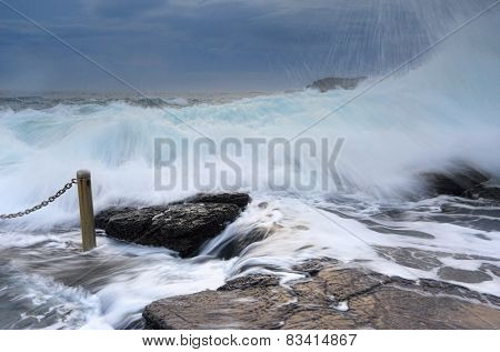 Bracing As Powerful Waves Come Crashing Over Rocks