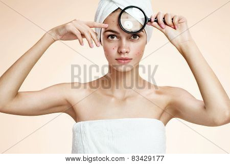 Girl with a pimply face holding magnifying glass