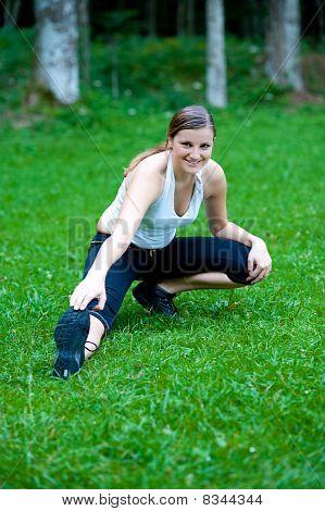 hübsch junges Mädchen Stretshes Bein on green grass