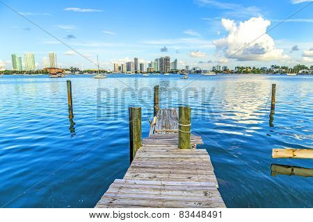 old wooden pier with view to modern skyline of Miami under blue sky poster