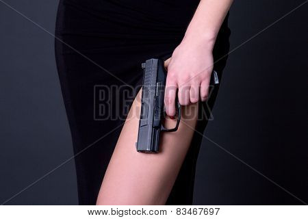 Sexy Woman In Black Dress Holding Gun Over Grey