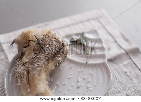 Cooked on steam grenadier fish with sea salt and fresh rosemary on white plate