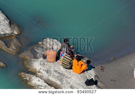 Indian Family Sitting On A Rock At The River Ganga