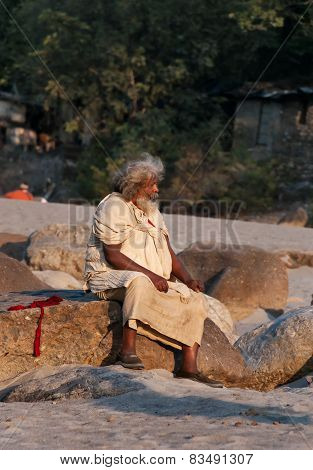 Indian Man Sits On Rock At The Beach Near River Ganga