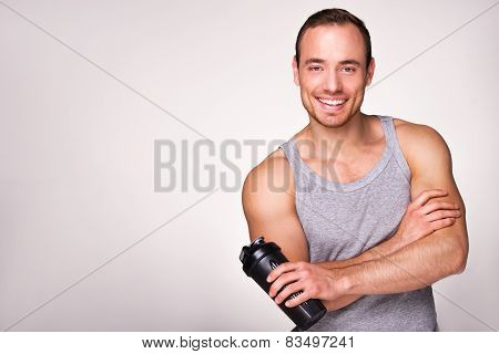 Young sporty man with sport shaker