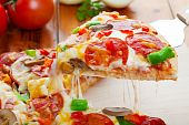 A slice of hot pizza deluxe with pepperoni mushrooms peppers & lots of gooey mozzarella cheese ready to be served. poster